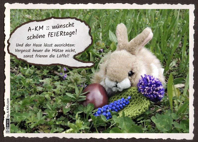 Plüschhase sitzt mit Osterei und Wollmütze im Gras - und schaut mürrisch.