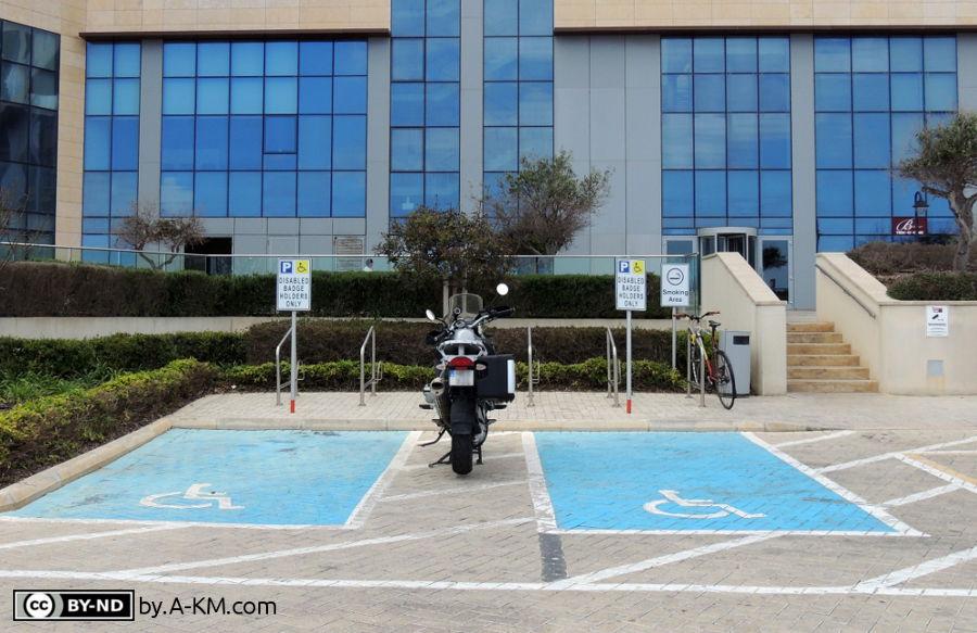 Motorrad parkt zwischen den Behindertenparkplätzen und macht sie so unbenutzbar - Barrierefreiheit gehört erklärt.